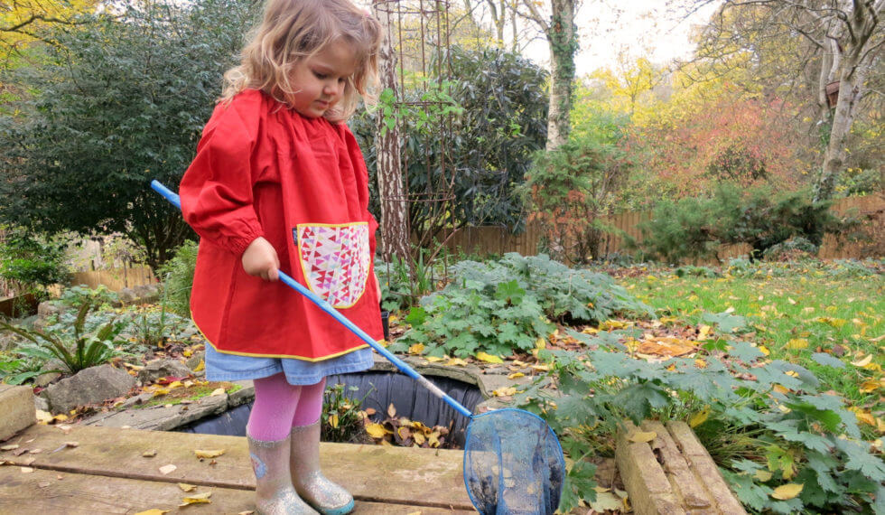 Child wearing red linen smock in garden